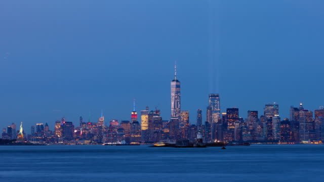 Lower Manhattan at dusk with the two beams of lights from the Tribute in Light. New York City Harbor - vídeo