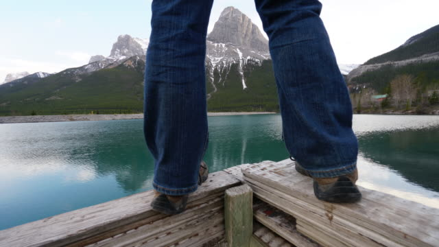 lower torso of man, standing on dock, mountains - эскапизм стоковые видео и кадры b-roll