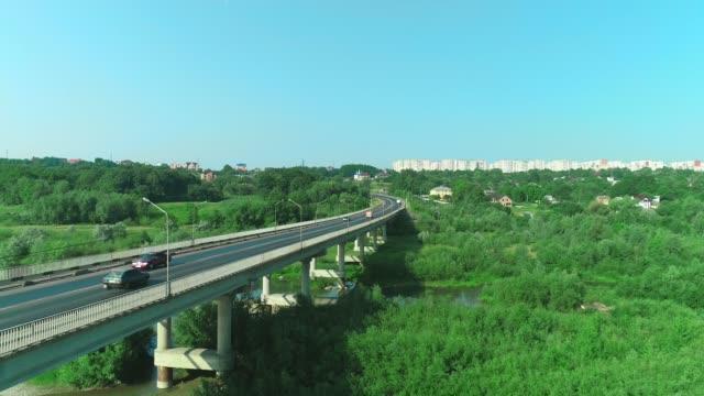 stockvideo's en b-roll-footage met het verlagen van de hoogte luchtfoto van stevige brug en auto's bewegen langs het en pittoreske stadgebied. 4k. - maastricht
