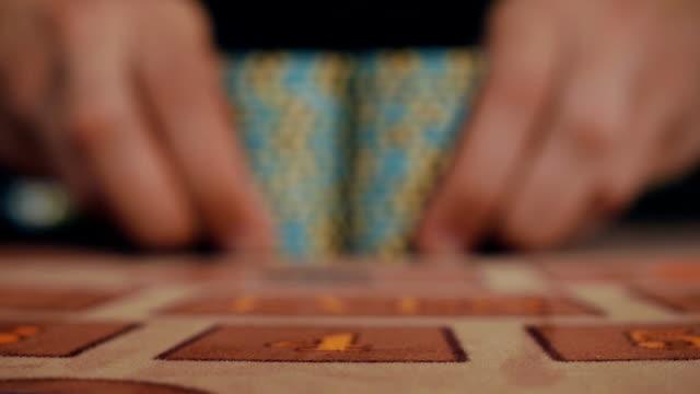 luck smiled player. the dealer moves the player's winnings - feltro video stock e b–roll