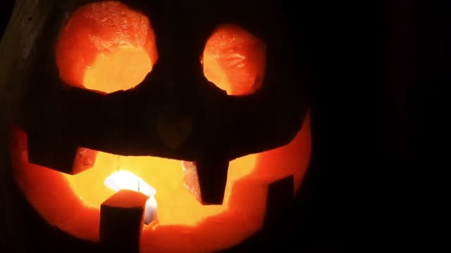Lucky laughing Halloween pumpkin. Jack-o'-lantern for Halloween with a burning candle inside video