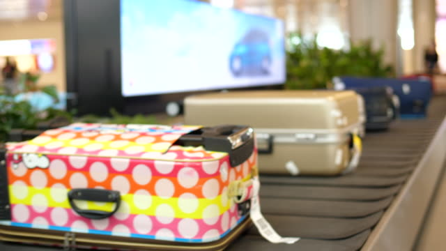 gepäckgurt in der ankunftshalle am flughafen - karo stock-videos und b-roll-filmmaterial