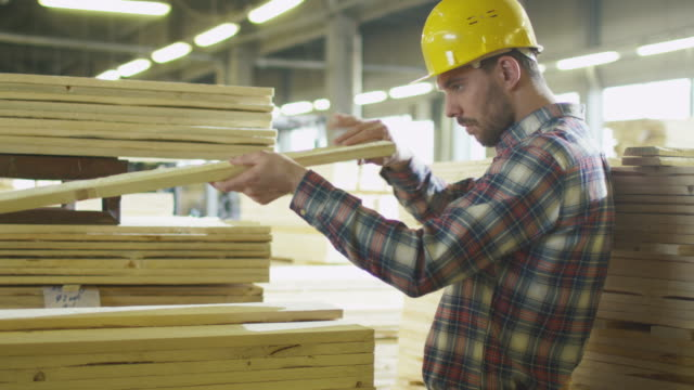 Lumber mill worker makes quality control of the wood in a warehouse.