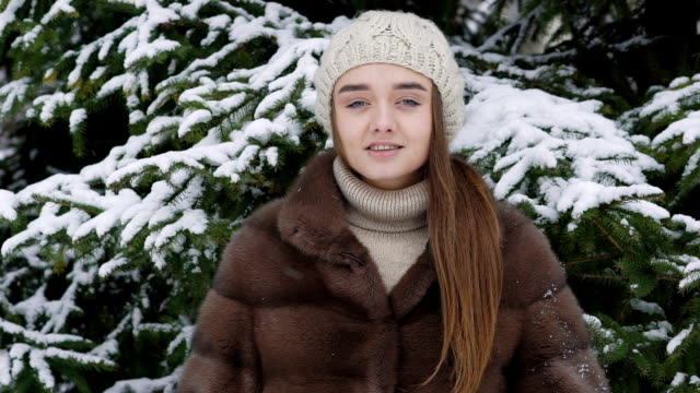 A lump of snow falling on the girl standing near tree. Slow motion video