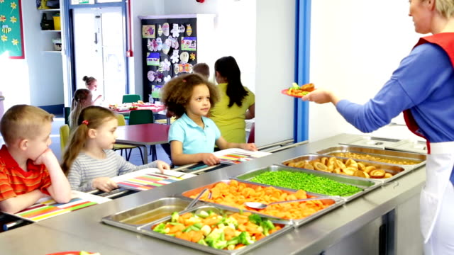 Lunch Time Children School children take it in turn to get their lunch from the school canteen cafeteria stock videos & royalty-free footage