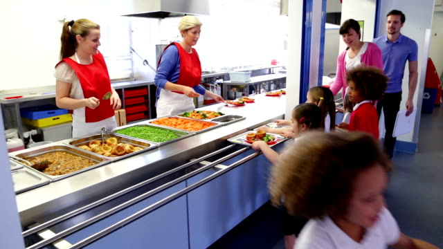 Lunch time! School children take it in turn to get their lunch from the school canteen cafeteria stock videos & royalty-free footage