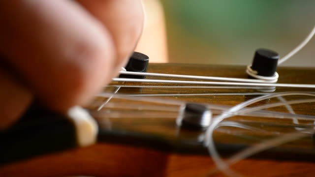 luthier placing the chord of a guitar, close up - ackord bildbanksvideor och videomaterial från bakom kulisserna