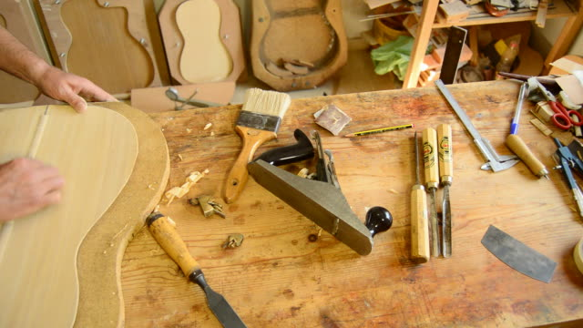 Luthier sanding a guitar, pan video