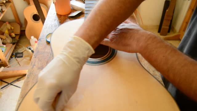 Luthier varnishing a guitar, tilt video
