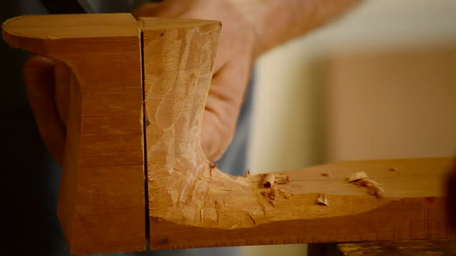 Luthier with chisel making a guitar mastil, close up video