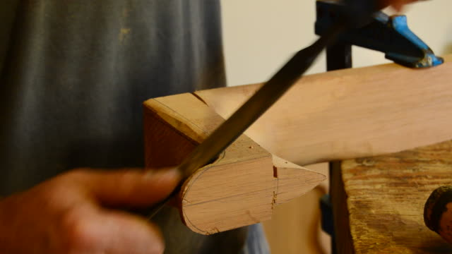 Luthier with rasp in a fabrication of a guitar's mastil video