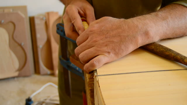 Luthier working with chisel in close up video