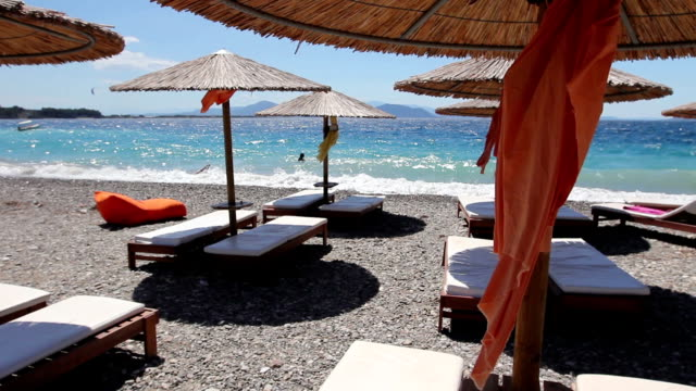 Luxurious fashion loungers, sunbed with umbrella for relaxing by the sandy beach video