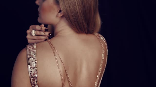 Luxurious girl and gold jewelry. Girls from the back in a brilliant elegant dress are holding golden chains in their hands. Jewelry for women. In the studio on a black background. dress stock videos & royalty-free footage
