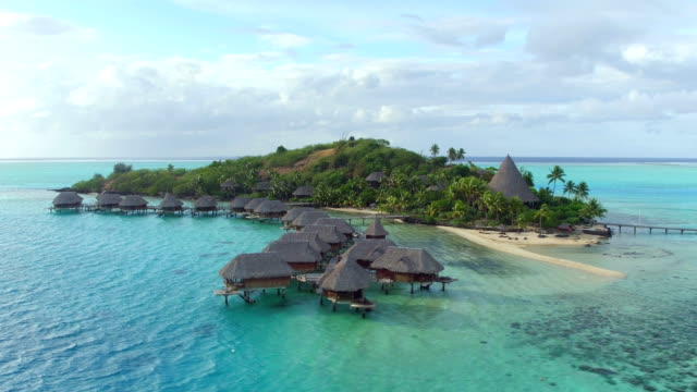 AERIAL: Luxurious private island resort with deluxe overwater bungalows and exclusive beachfront villas on small secluded motu island in Pacific ocean AERIAL: Luxurious private island resort with deluxe overwater bungalows and exclusive beachfront villas on small secluded motu island in Pacific ocean military private stock videos & royalty-free footage