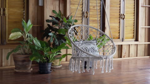 Luxury bespoke indoor boho hanging chair A luxury log cabin villa with hardwood floor and wood paneling walls.  Sparsely decorated with handmade bespoke indoor porch swing and several houseplants. boho stock videos & royalty-free footage