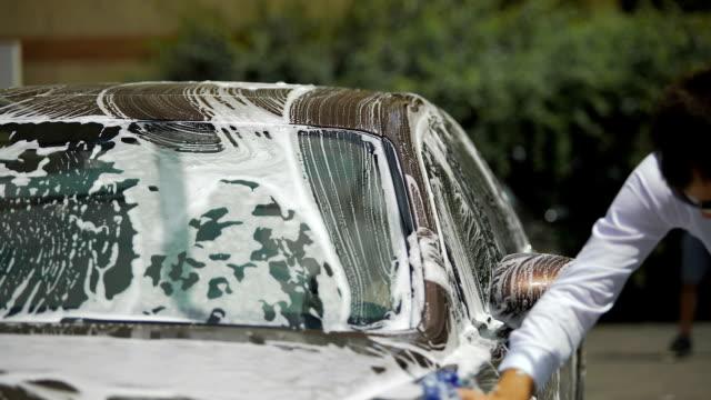 luxury biltvätt service, person rengöring auto med tvål svamp, transport - surf garage bildbanksvideor och videomaterial från bakom kulisserna
