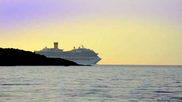 Luxury cruise ship sailing on ocean sunset horizon video