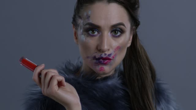 luxury fashion model in fur holds red lipstick. fashion video. - clavicola video stock e b–roll
