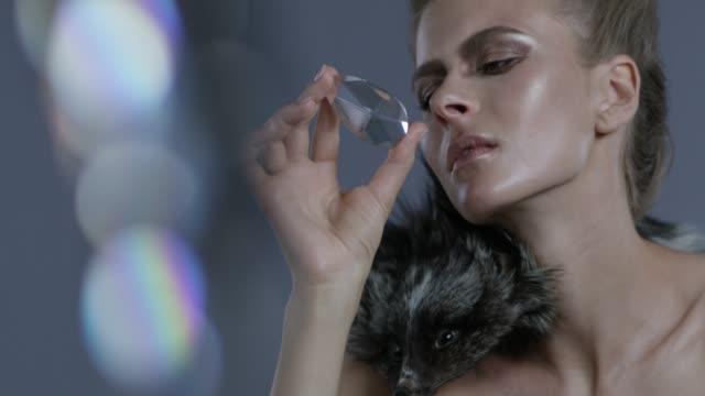 luxury fashion model wearing fur holds a diamond. fashion video. - femminilità video stock e b–roll
