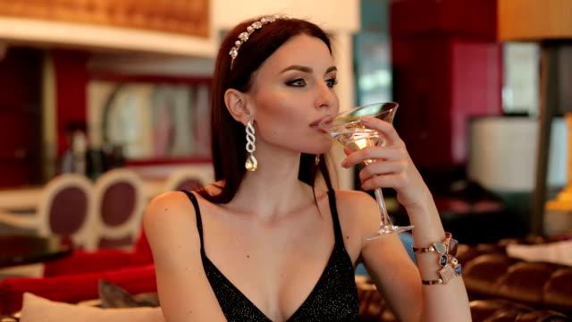 stockvideo's en b-roll-footage met luxe meisje een martini drinken in een restaurant. - martini