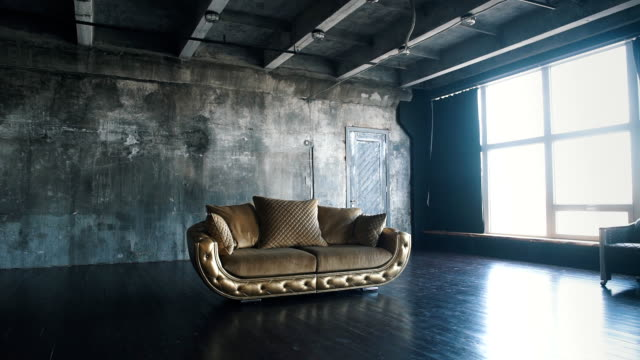 Luxury golden sofa on a loft background luxury quilted sofa in the Studio in gold color,Luxury golden sofa on a loft background.Beautiful sofa at a window in a modern apartment,slow motion loft apartment stock videos & royalty-free footage