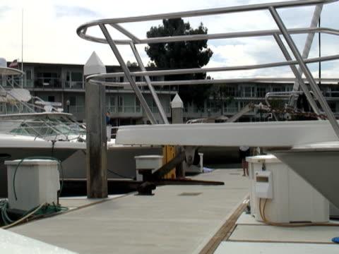 luxury lifestyle: man on dock - passes boat bow - bir orta yetişkin erkek sadece stok videoları ve detay görüntü çekimi