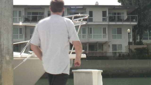 (hd1080i) luxury lifestyle: man on dock - passes boat, building - {{searchview.contributor.websiteurl}} stock videos & royalty-free footage