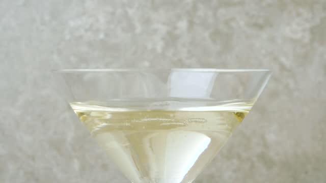 stockvideo's en b-roll-footage met luxe martini. de hand giet zoete martini in leeg glas tegen lichte achtergrond. vermout spetterende golven, cocktailparty. slow motion. close-up - martini