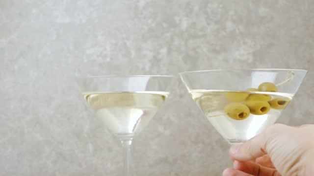 lyx martini. hand sätter ett glas med martini på bordet dekorerad med oliver, cocktailpinnar, lime och mynta mot ljus bakgrund. mittskott. 4k - martini bildbanksvideor och videomaterial från bakom kulisserna