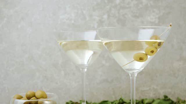 stockvideo's en b-roll-footage met luxe martini. hand legt een drie groene olijven op cocktailstok in glas met martini op de lijst die met cocktailstokken, kalk en munt tegen lichte achtergrond wordt verfraaid. middenschot. 4k - martini