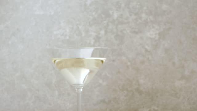stockvideo's en b-roll-footage met luxe martini. de hand neemt een glas met martini van de lijst die met olijven, cocktailstokken, kalk en munt tegen lichte achtergrond wordt verfraaid. middenschot. 4k - martini