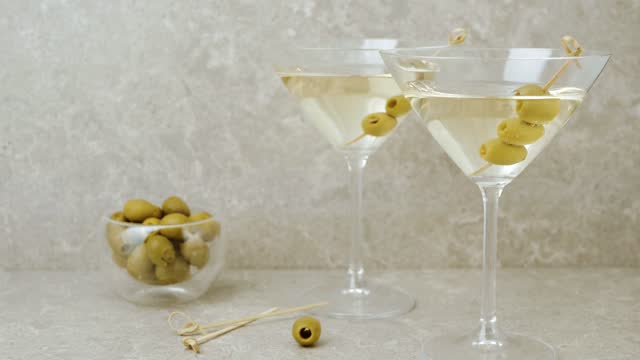 stockvideo's en b-roll-footage met luxe martini. lijst die met cocktailstokken, olijven en glas met martini tegen lichte achtergrond wordt verfraaid. camera beweegt zich omhoog van de olijven op glas met martini. breed schot. 4k - martini