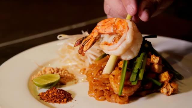 lyxiga förbereder en stor räka på pad thai maträtt. slow motion - böngrodd bildbanksvideor och videomaterial från bakom kulisserna
