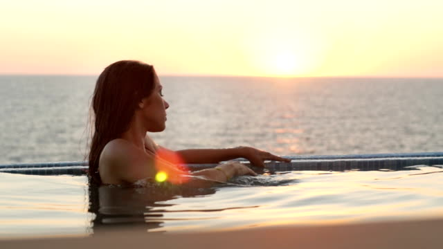 Luxury resort woman relaxing in infinity swimming pool Luxury resort woman relaxing in infinity swimming pool spa treatment stock videos & royalty-free footage