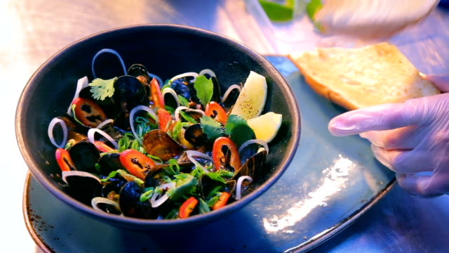 Luxury seafood restaurant delicious dish presentation - fresh mussels served with vegetables and croutons video