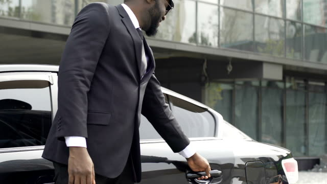Luxury taxi driver opening door for wealthy client, inviting for ride, services Luxury taxi driver opening door for wealthy client, inviting for ride, services military private stock videos & royalty-free footage