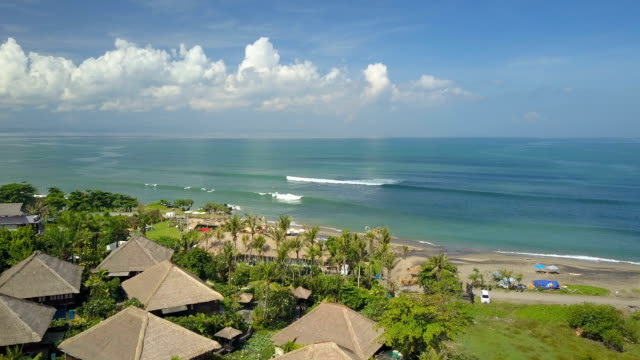 しぶき海とエキゾチックな砂浜を見下ろす空中: 高級観光リゾート - ヴィラ点の映像素材/bロール
