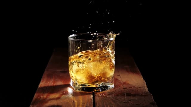 Luxury whiskey. Ice cubes fall with splashes into a glass with golden whisky on the brown wooden table against black background. Scotch in tumbler. Bourbon in highball.