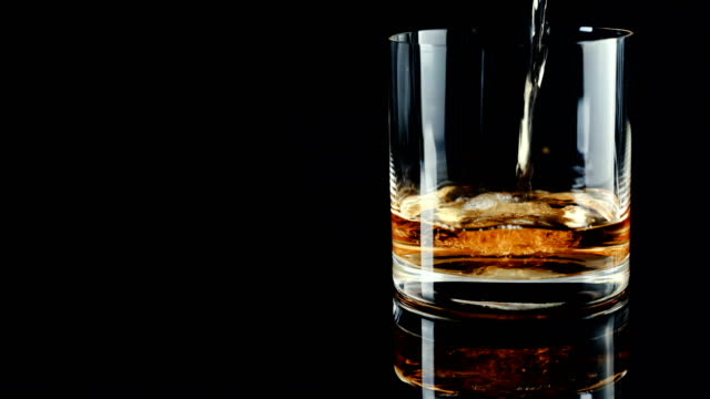 luxury whisky poured to empty glass - rum superalcolico video stock e b–roll