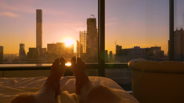POV: Lying in bed and watching the sun rise from behind the modern skyscrapers.