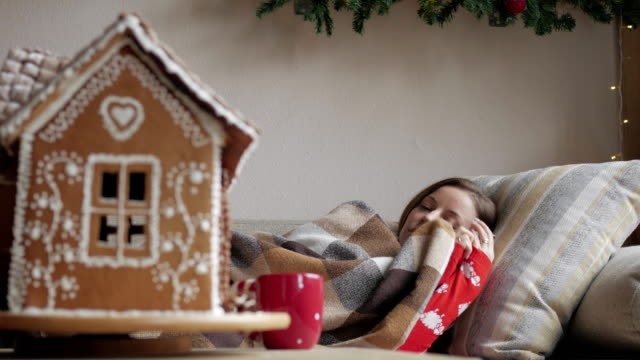 lying on the sofa under a blanket. health and illness concept - of diseased woman with cup of tea. Christmas morning. video