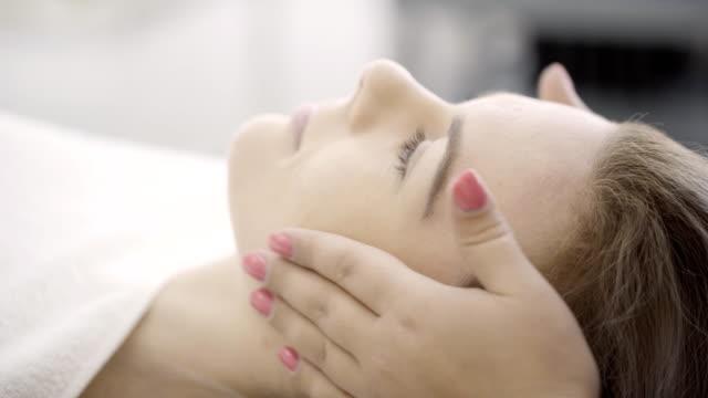 vidéos et rushes de mains de femme couchée faire un massage du visage avec des mouvements légers - soin spa
