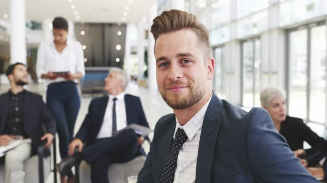 I'm closer than I was yesterday 4k video footage of a young businessman smiling in an office with his colleagues in the background suit videos stock videos & royalty-free footage