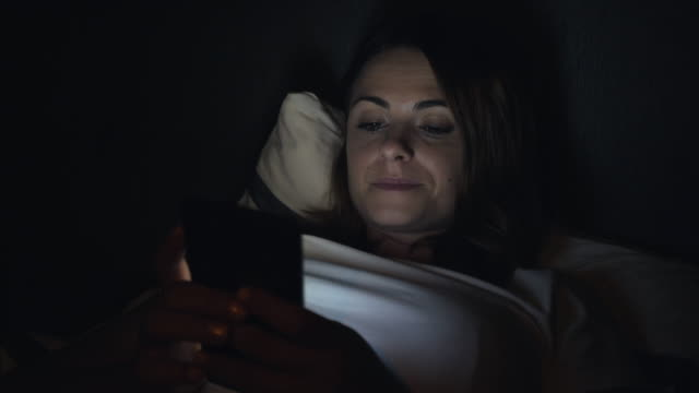 I`m connected with my smart phone. Young woman using smart phone late in night. insomnia stock videos & royalty-free footage