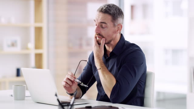 I'm starting to feel the pressure 4k video footage of a handsome mature businessman sitting alone in his office and feeling stressed while using his laptop exhaustion stock videos & royalty-free footage