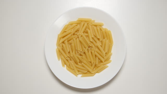 TOP VIEW: Macaroni appear on a white dish on a white table (stop motion) video