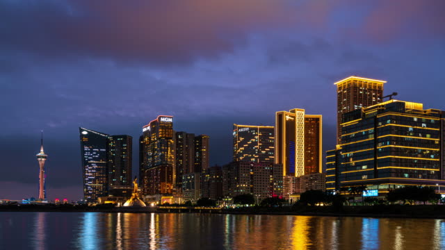Macau or Macao cityscape during dusk, all hotel and tower are colorful lighten up with blue sky. It is panoramic scene for Macau Island. There is a Kun Lam Statue that build by Portuguese Government in the centre.