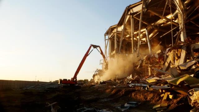 machine disassembles old hockey stadium in spring evening