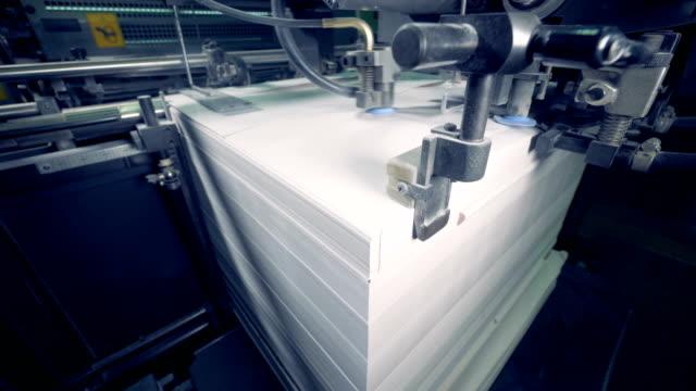 a machine divides lot of paper sheets, close up. paper production process. - мембрана клетки стоковые видео и кадры b-roll